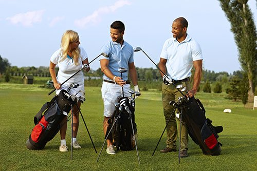 Three Golfers Pulling Clubs From Golf Bags