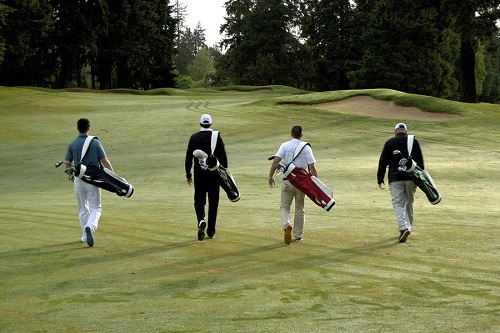 Four Golfers with Golf Bags Leaving Golf Court